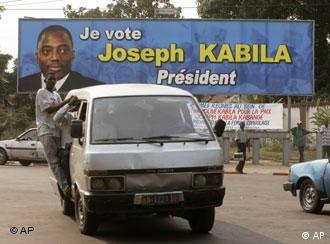 Ein voll besetzter Taxibus vor einem Kabila-Plakat in Kinshasa