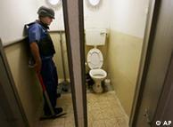 An Israeli plumber checks a toilet in a Tel Aviv bomb shelter