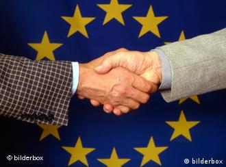 A handshake takes place in front of the European Union flag
