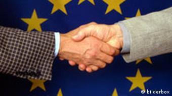 Handshake in front of the EU emblem