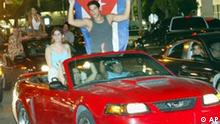 A couple, one carrying a cuban flag, ride on the back of a convertible as they join other revelers as they cruise the streets of Hialeah, Fla., in the early morning hours of Aug. 1, 2006, after hearing the news about Fidel Castro's health. Cuban officials announced the head of Cuba had temporarily relinquished presidential power to his brother Raul due to an intestinal illness. (AP Photo/Wilfredo Lee)