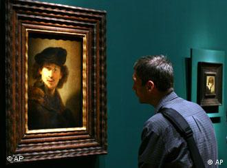 A man looks at a self-portrait of Rembrandt (1634) in Berlin's Gemaelde Galerie
