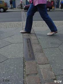 A person steps over the plaque embedded in the streets that marks the course of the Berlin Wall