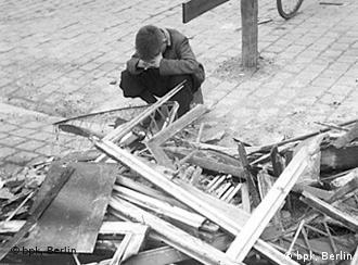 Black-and-white photo from 1954 of a boy kneeling in front of a pile of wood that was part of a house