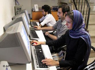People sat at computers in an internet cafe in Iran