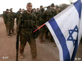 Israeli soldiers, one holding an Israeli flag