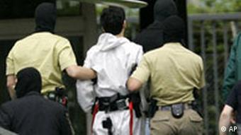 Police lead a terror suspect away for questioning