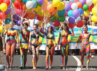 A row of colorfully painted women with balloons