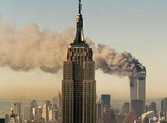 The World Trade Center burns behind the Empire State Building on 9/11
