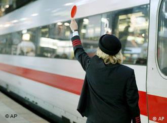 Train conductor holding a red sign near a stopped train
