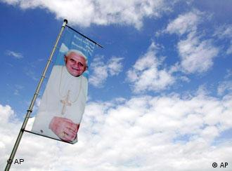A flag with the photo of Pope Benedict XVI fluttering int he wind against the blue sky