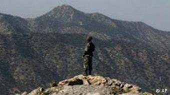 A Pakistan army soldier stands alert as he monitors the Afghan-Pakistan border