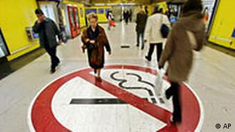 People walk over a large no smoking sign