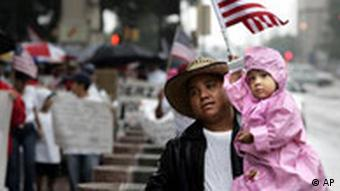 Man carries his two-year-old daughter, during an immigrant rights march in downtown Dallas