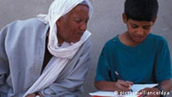 Old man looking at boy who is writing in a textbook