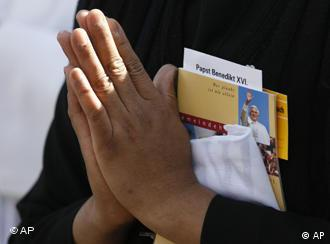 A praying nun folds her hands holding a songbook