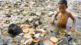 Indonesisches Kind steht in Müll und Schmutzwasser. Quelle: dpa