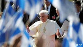 Pope Benedict XVI is seen waving through Bavarian flags after his arrival at the airport of Munich