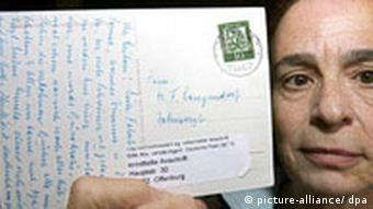 A woman holding up a postcard that traveled 44 years