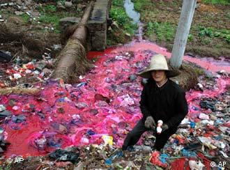 A woman collects plastic bottles near a river where water is polluted with a reddish dye directly discharged from a small paper factory nearby in Dongxiang, in east China's Jiangxi Province in this March 25, 2005 file photo. China needs to break ties between polluting industries and local officials if it is to succeed in cleaning up its badly tainted water supplies, the founder of a new environmental group said Tuesday, Sept. 18, 2006. (AP Photo, File) ** CHINA OUT **