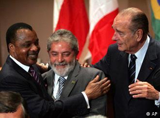 El presidente francés, Jacques Chirac observa el abrazo entre sus homólogos de Brasil y del Congo.