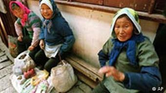 Three women sell products from their farms, including medicinal herbs, on a side street side in the outskirts of Shanghai, China Friday June 11, 1999. (AP Photo/Eugene Hoshiko)