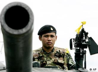 A Thai soldier takes position atop a tank while monitoring the highway for a possible resistance group after the coup on the outskirts of Bangkok, Thailand Thursday, Sept. 21, 2006. The Tuesday bloodless coup led by Army commander Gen. Sondhi Boonyaratkalin has been enthusiastically received by many Thais but sharply criticized by Western governments as a blow against democracy. (AP Photo/Apichart Weerawong)