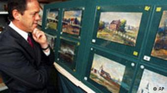 Auctioneer Ian Morris views some of the Adolf Hitler paintings going up for auction