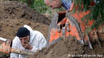 Two men bent over the burial site in Menden
