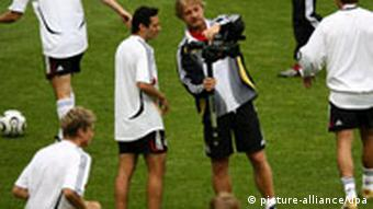 Wortmann explains the camera to a player during a training session