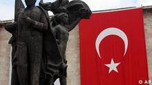 A statue of modern Turkey's founder Mustafa Kemal Ataturk is seen next to a national flag in front of the Parliament before the formal opening of the legislative year in Ankara, Sunday, Oct. 1, 2006. Turkey's staunchly pro-secular President Ahmet Necdet Sezer warned on Sunday of a continued Islamic fundamentalist threat to Turkey and said the military, the traditional guardians of the secular system, must be kept powerful. (AP Photo/Burhan Ozbilici)