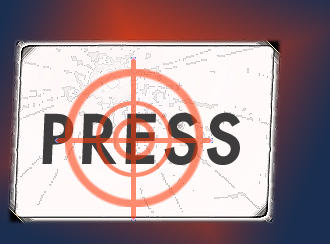 The word 'press' on a sign with in the center of a set of crosshairs