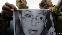 A woman holds a photograph of recently killed reporter Anna Politkovskaya during a rally on Pushkin square in downtown Moscow, Sunday, Oct. 8, 2006. The rally had been called to voice criticism of the deportation of more than 100 Georgians and closure of Georgian-owned restaurants and businesses in Moscow in the wake of Russia's bitter spy row with its small southern neighbor. But Saturday's apparent contract killing of Politkovskaya, a fierce critic of the war in Chechnya who had tirelessly uncovered abuses against civilians, became a major focus of the protest meeting. (AP Photo / Dmitry Lovetsky)