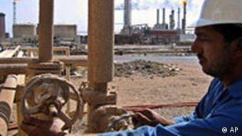 A worker operates the valves at the oil fields of Rumailah, near the southern city of Basra, Iraq