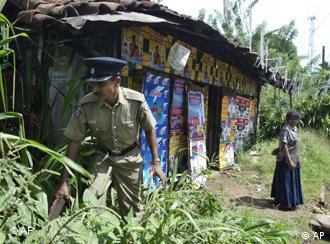 A Sri Lankan policeman searches for explosive devices after recovering a roadside mine at Kadawatha, a suburb of Colombo, Sri Lanka, Thursday, Oct. 19, 2006. The army defused a roadside bomb hidden in a garbage pile on the side of a main road on the outskirts of the capital, Colombo, according to police. (AP Photo/Eranga Jayawardena)