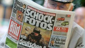 A man reads a newspaper which headlines shock photos from Afghanistan