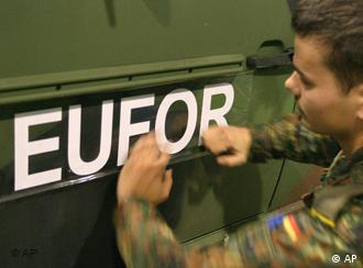 A soldier sticking a EUFOR sign to the side of a vehicle