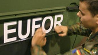 A German soldier attaches a EUFOR sign to a vehicle