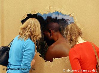 Two women looking through hole in the wall