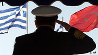 A Greek admiral (with his back to the camera) salutes, with Greek and Turkish flags in the background.