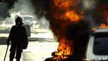 A Mexican federal police officer walks next to a burning car as he looks for protesters near Oaxaca University Thursday, Nov. 2, 2006, in Mexico. The protesters are demanding the resignation of Oaxaca Gov. Ulises Ruiz, whom they accuse of rigging the 2004 election to win office and organizing bands of thugs to attack dissidents. (AP Photo/Guillermo Arias)