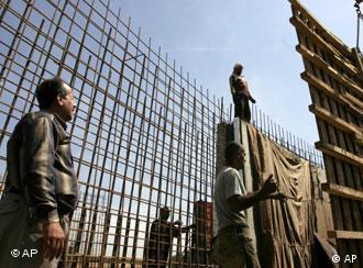 Iraqi construction workers manuever a piec of steel in Baghdad