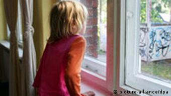 A small girl looks out of a window