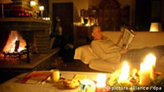 A women reads a book by candlelight in her living room during a power outage