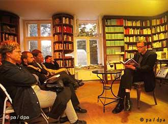 A salon, with a group sitting on chairs and surrounded by books looking through some literature