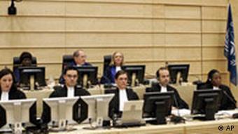Männer und Frauen in schwarzen Roben sitzen in zwei Reihen jeweils vor Bildschirmen (Quelle: AP)