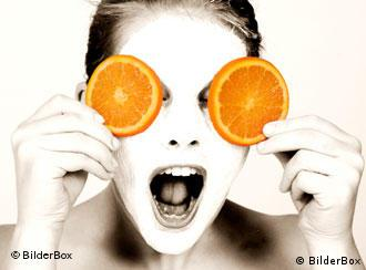 woman with white beauty mask and orange slices over her eyes