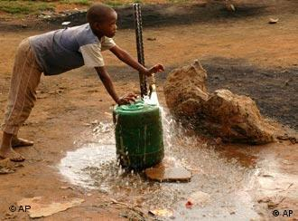 An African child fills a container with water for domestic use