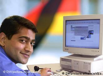 indian man sitting at computer with germany flag