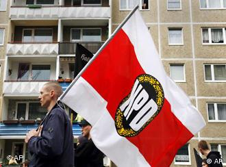 A skinhead in a demonstration, carrying an NPD flag
